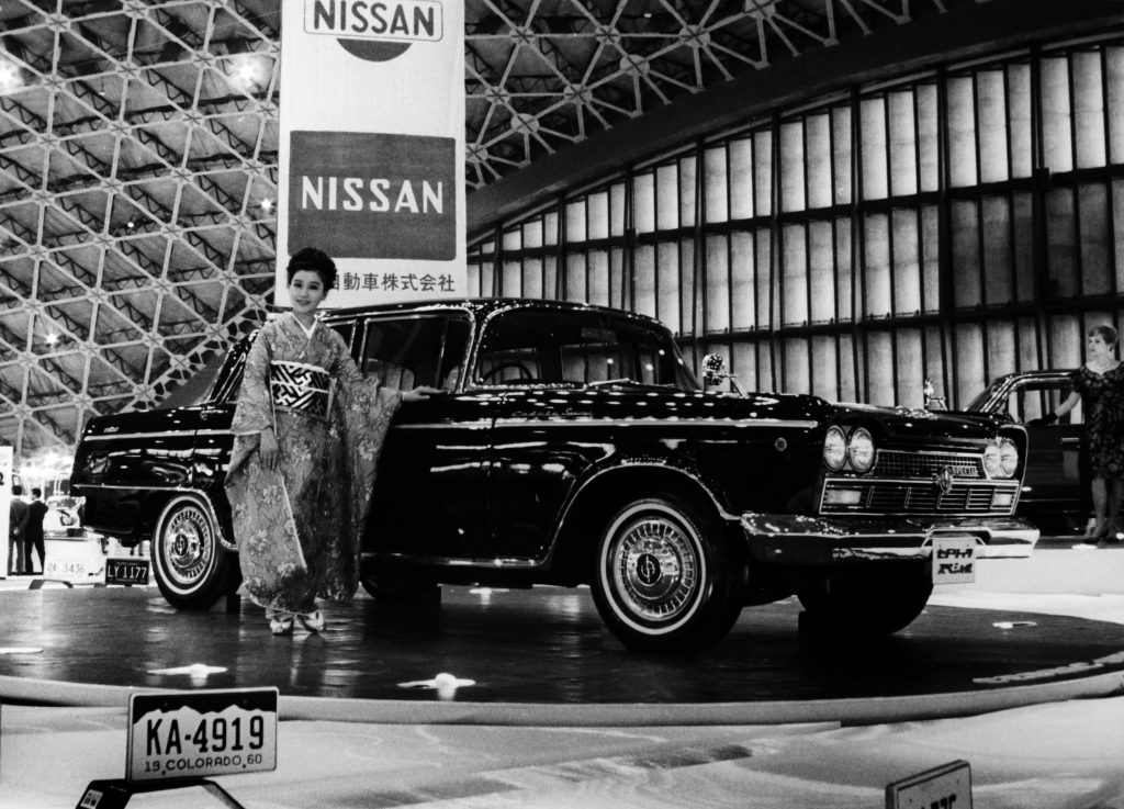 A black and white archival photo of a dark Nissan Cedric sedan being displayed by a woman in a kimono