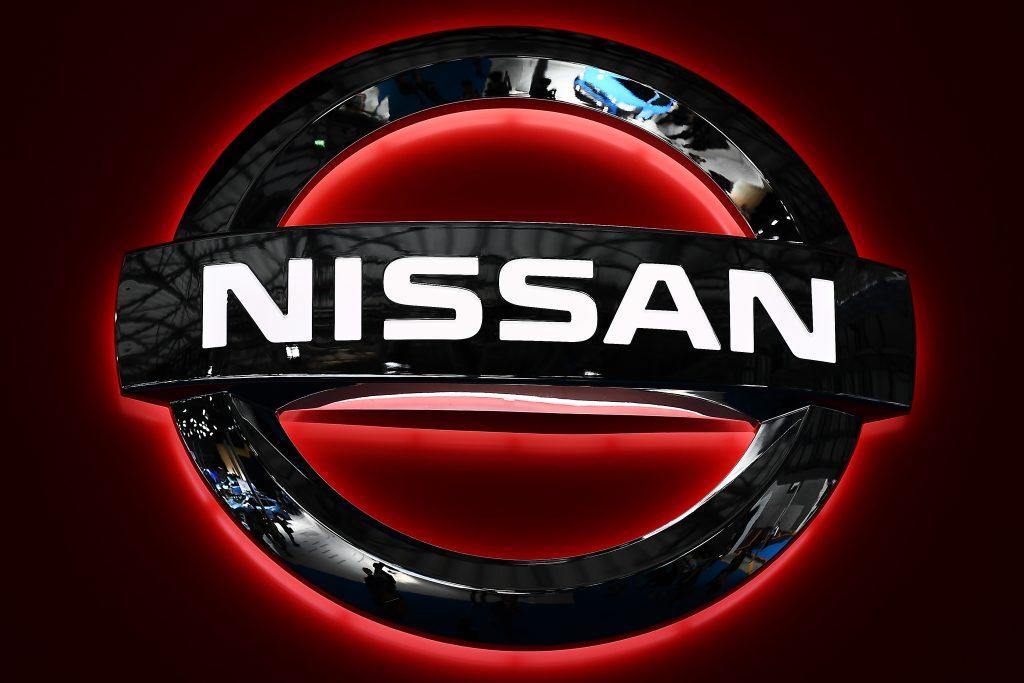 A black Nissan logo backlit in red