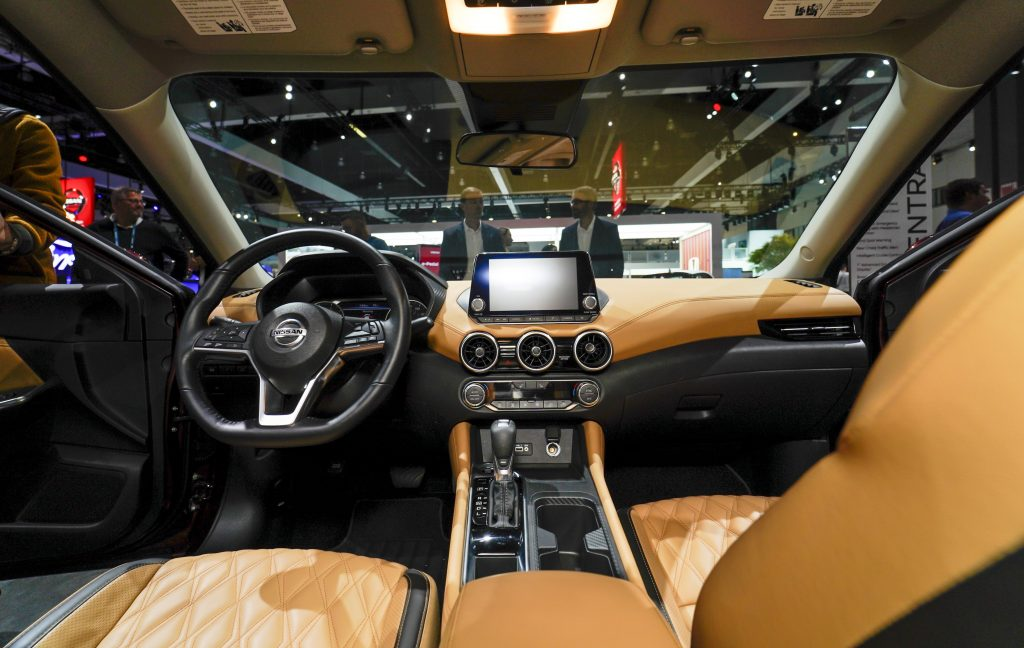 The tan interior of a nissan sentra as shown from behind the drivers seat