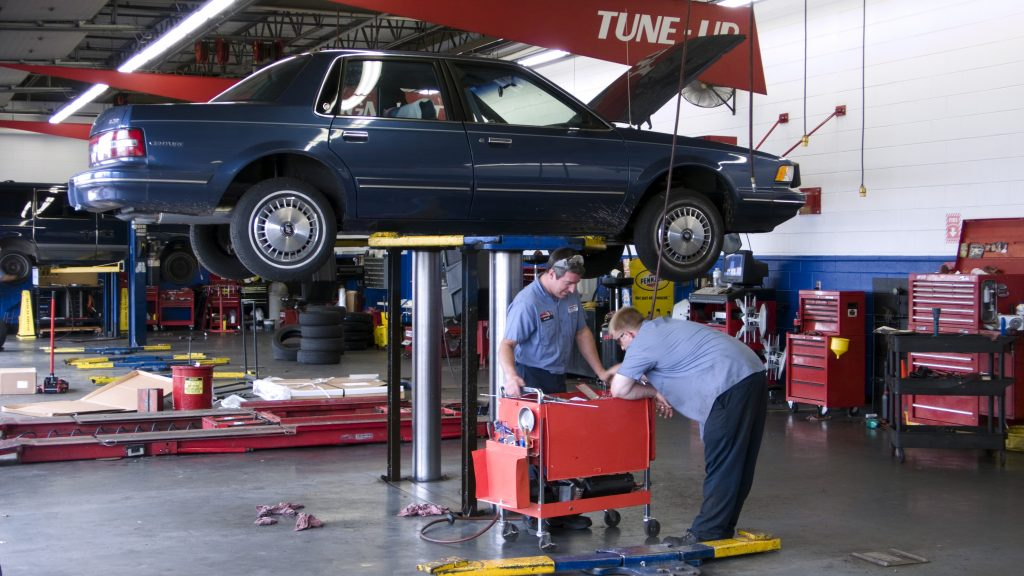 Motor car on hydraulic lift repair workshop. make sure to ask the mechanic plenty of questsions