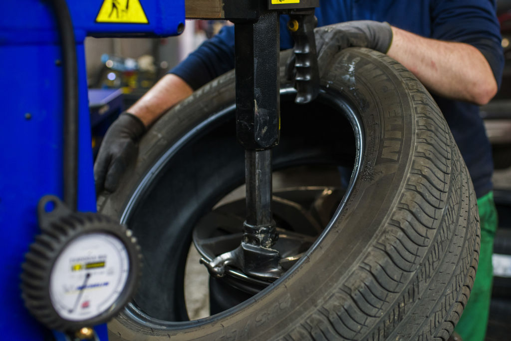 A Michelin tire being mounted onto a wheel hub
