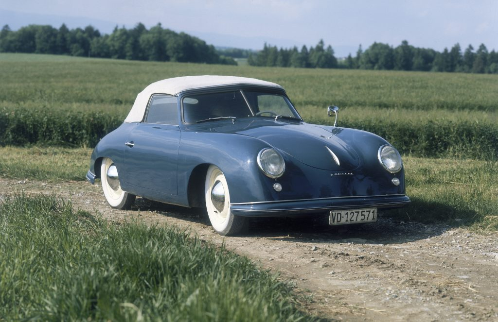 1951 Porsche 356 in blue with a white soft top parked in a field