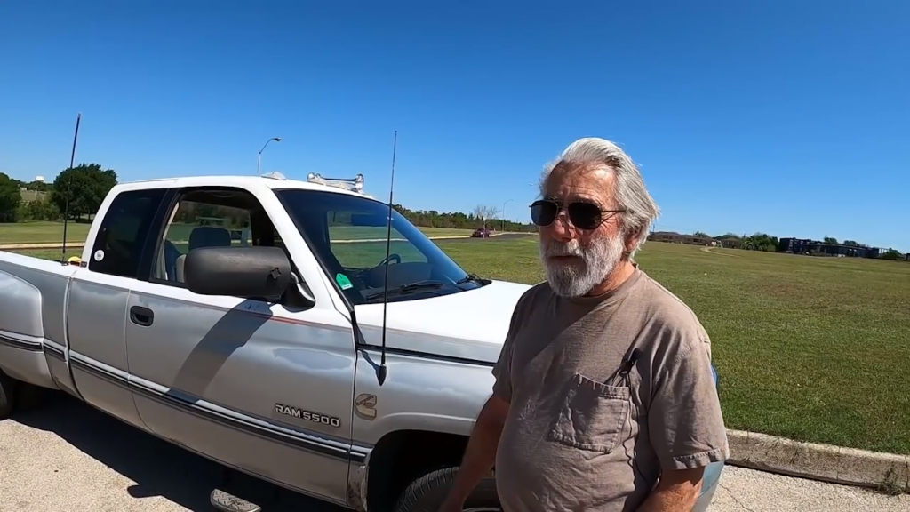 a 1997 Dodge Ram 3500 with its owner standing in front of it