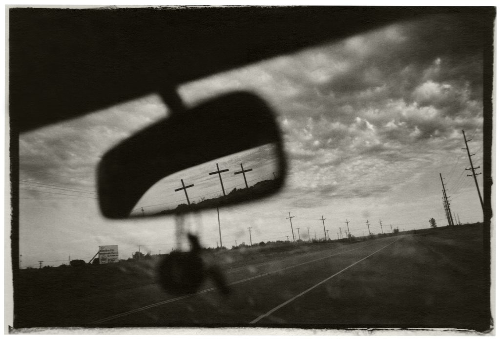 View of three crosses on the side of a highway, as seen through the rearview mirror of a car.