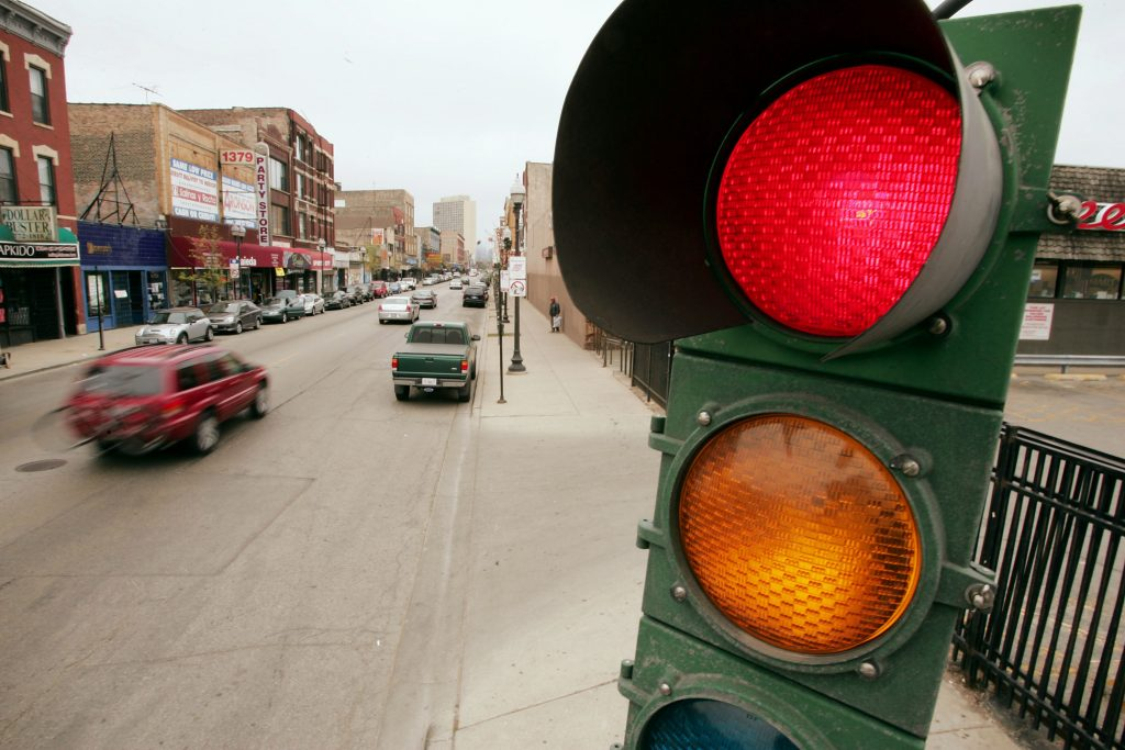 A picture of a traffic light that controls the flow of vehicles and pedestrians.