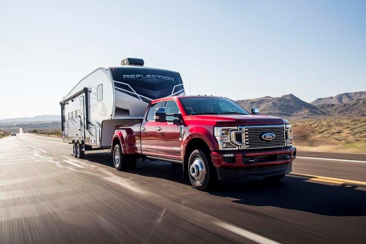 A red 2021 Ford F-350 Super Duty hauling a camper in a rural area