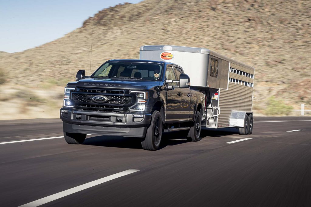 A blue 2020 Ford F-150 hauling a silver trailer in a hilly area
