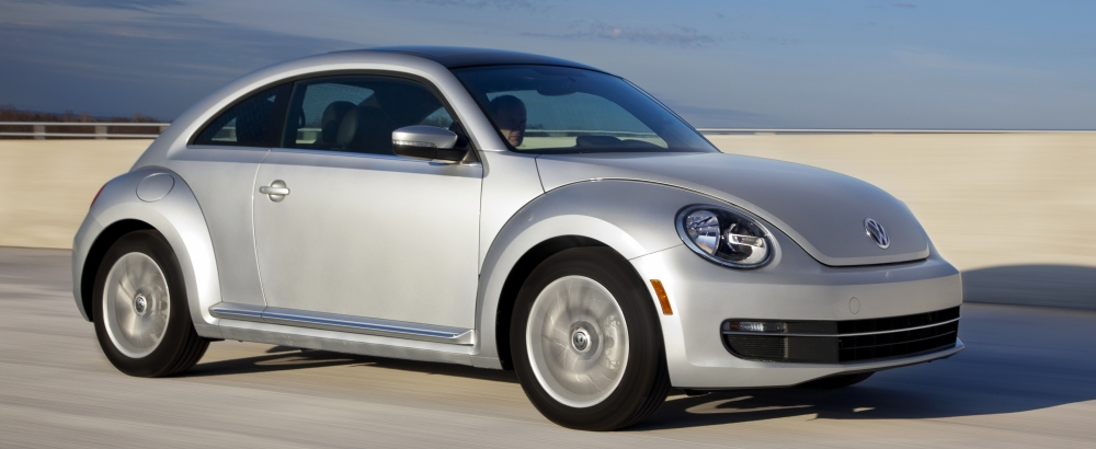 2013 Volkswagen Beetle driving on a bridge over a large body of water is now one of the best used cars under $10,000.