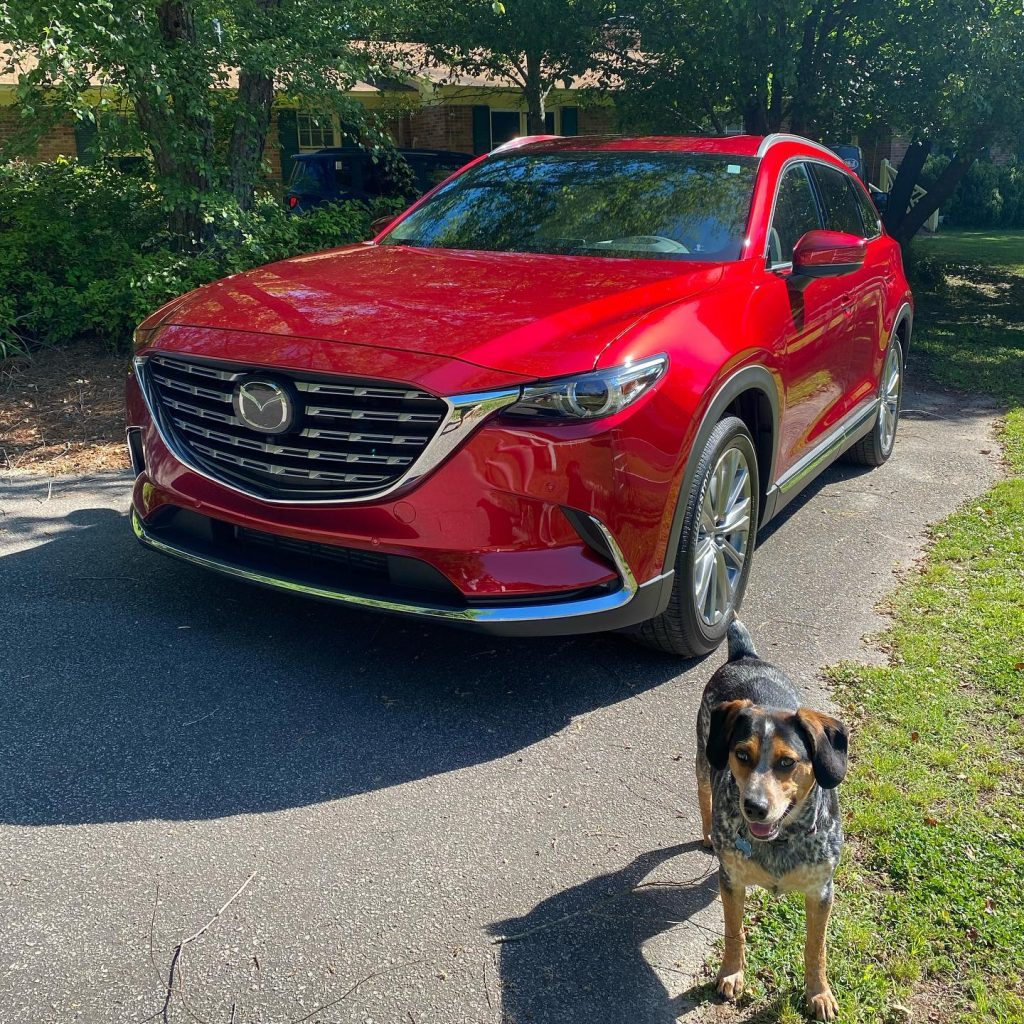 A red 2021 Mazda CX-9 parked in a drive way near an excited dog named Bruce