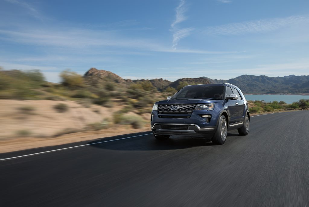 a blue 2018 Ford Explorer crossover SUV in a press photo driving on a scenic road near a lake.