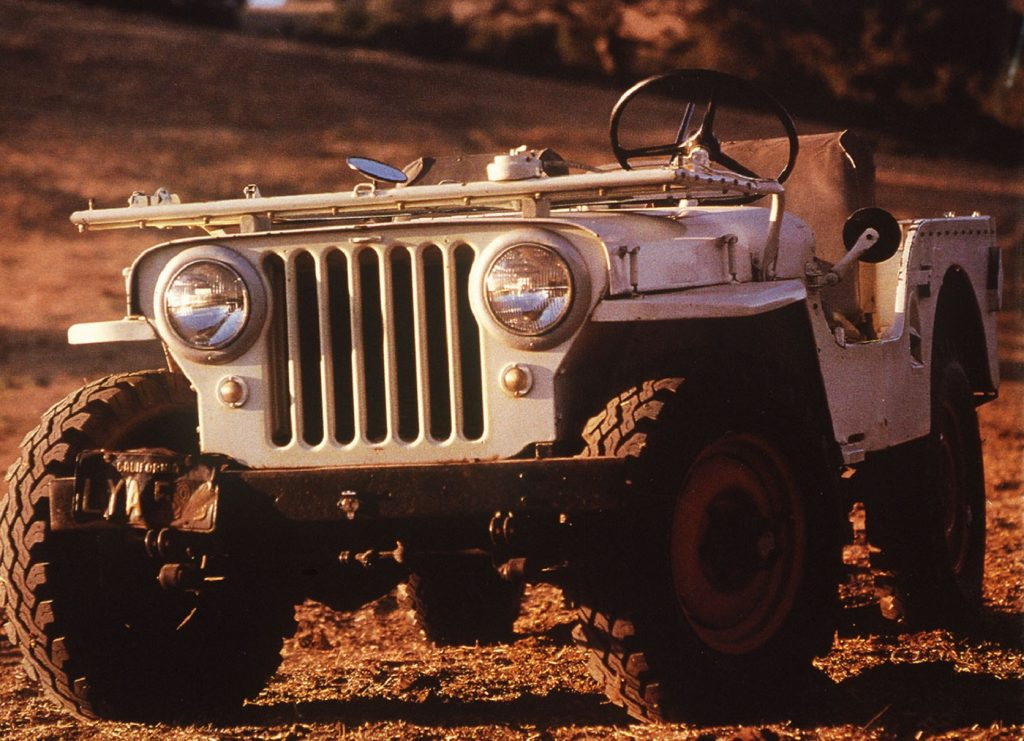 A white 1945 Jeep CJ-2A in a field with its windshield folded down