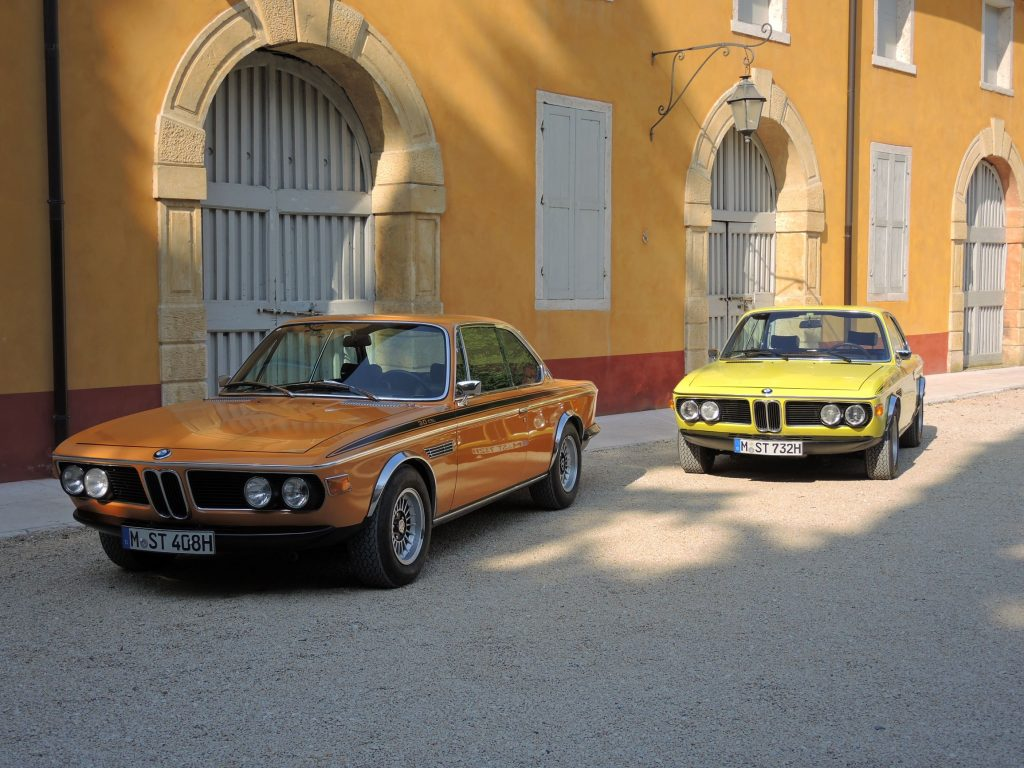 An orange and a yellow 1971 BMW 3.0 CSL by an orange-colored building