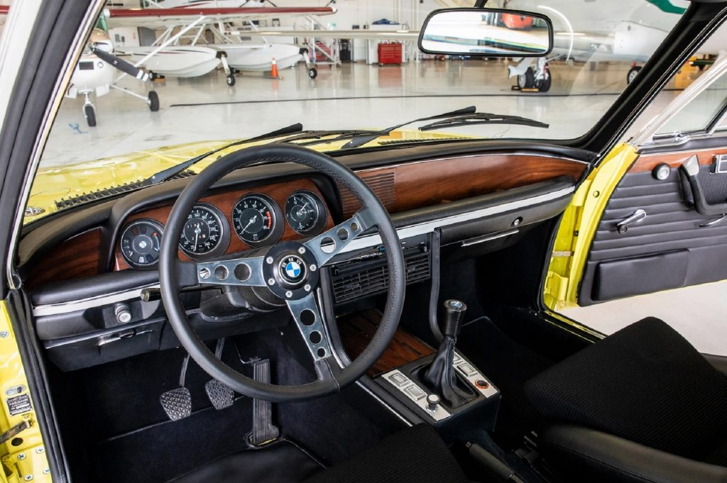 The black-leather front seats and wood dashboard of a yellow 1973 BMW 3.0 CSL