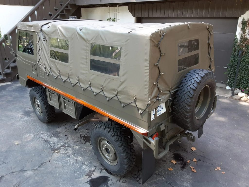 The rear 3/4 view of Bob Lutz's olive-green 1973 Steyr-Puch Pinzgauer 710M next to a brown house
