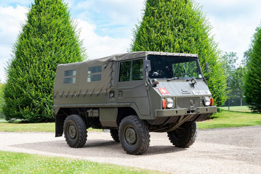 An olive-green 1975 Steyr-Puch Pinzgauer 710M on a tree-lined gravel path
