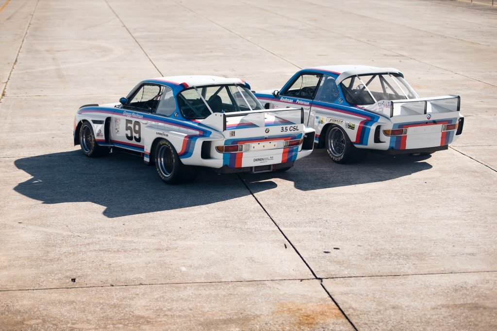 The rear 3/4 view of the No. 59 1976 BMW 3.0 CSL Batmobile next to the No. 26 1975 BMW 3.0 CSL Batmobile