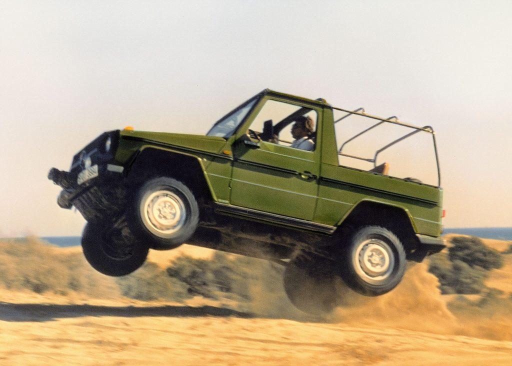 A green 1979 Mercedes G-Wagon Convertible jumping over sand