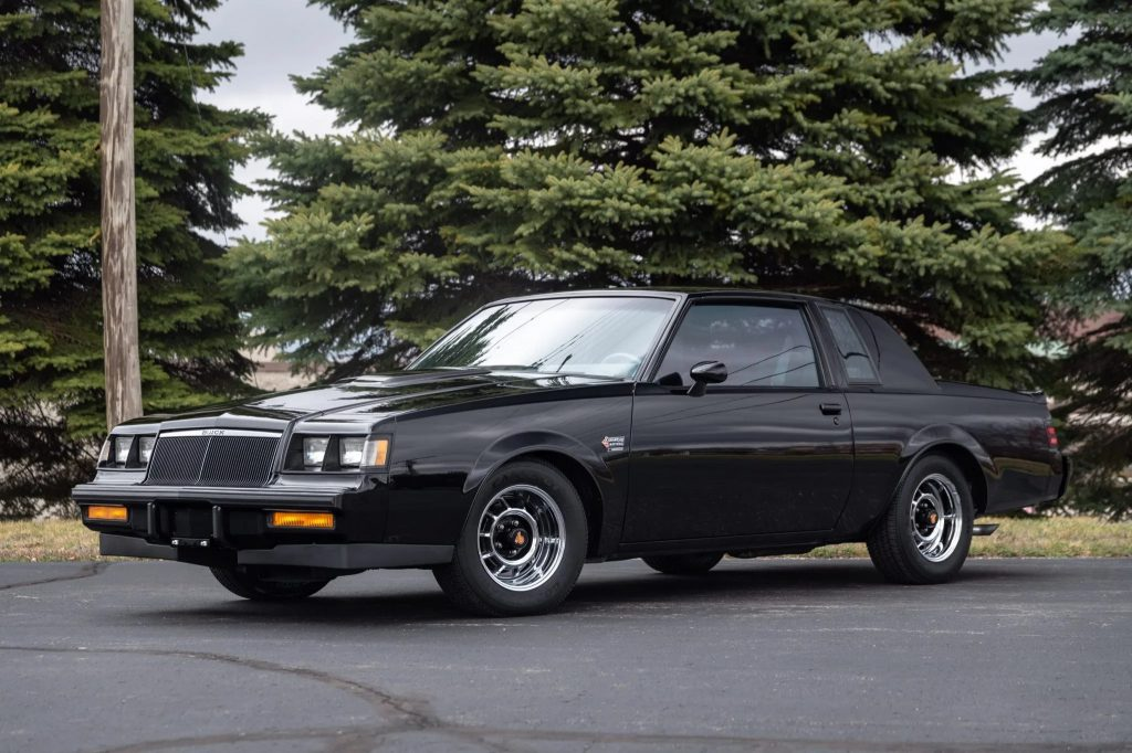 A black 1986 Buick Grand National in a tree-lined parking lot