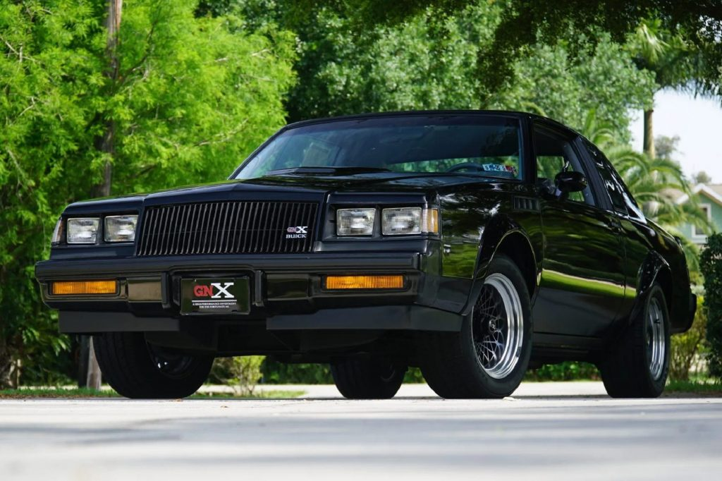 The front 3/4 view of a 262-mile black 1987 Buick GNX in a tree-lined parking lot