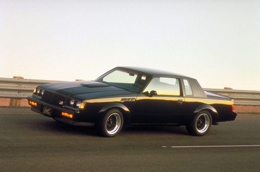 A black 1987 Buick GNX drives at high speeds down a road