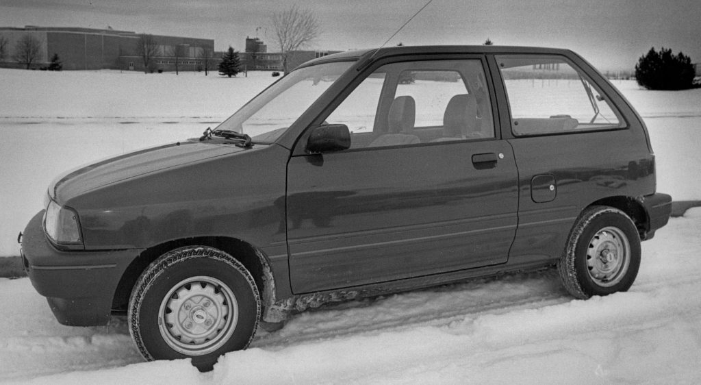 A black and white photo of a Ford Festiva compact car in the snow
