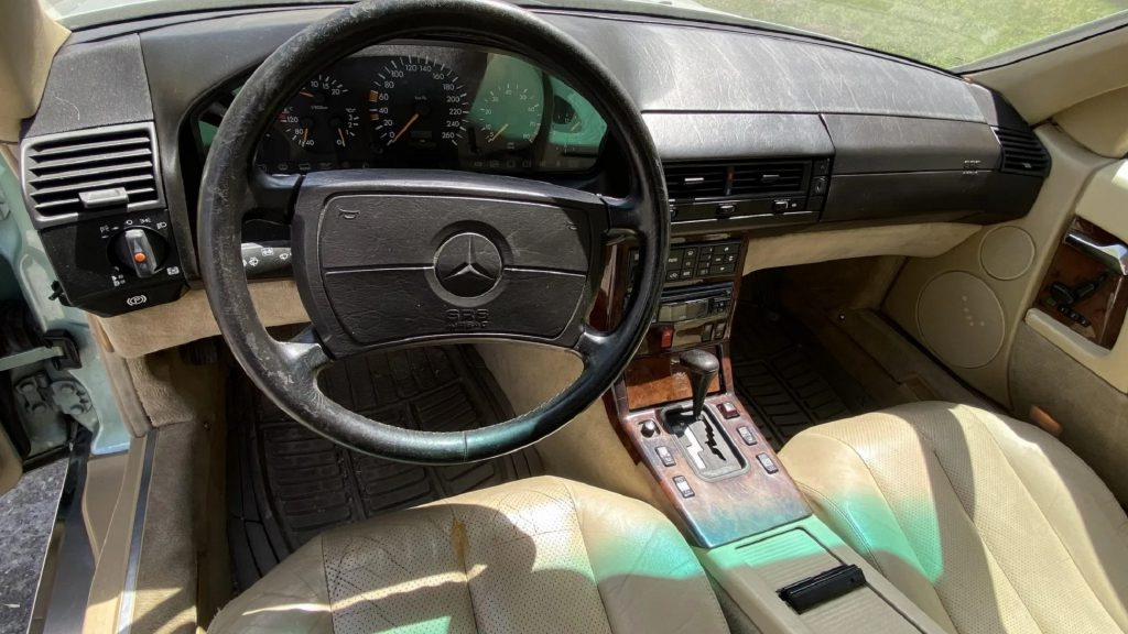 The tan-leather seats and wood-lined black dashboard of a 1991 Mercedes-Benz 300 SL