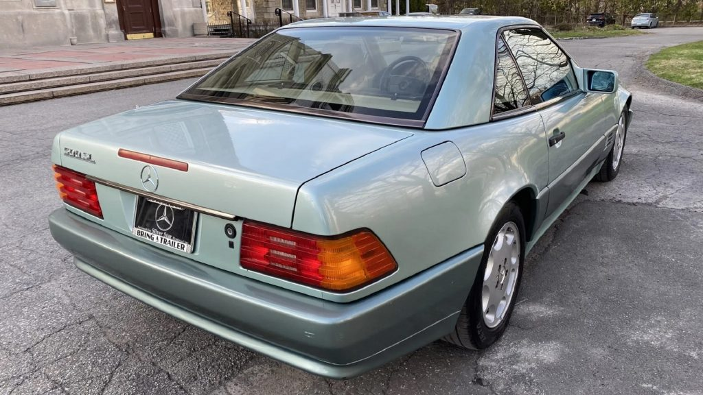 The rear 3/4 view of a two-tone-green 1991 Mercedes-Benz 300 SL with a hardtop and a 500 SL badge in a park parking lot