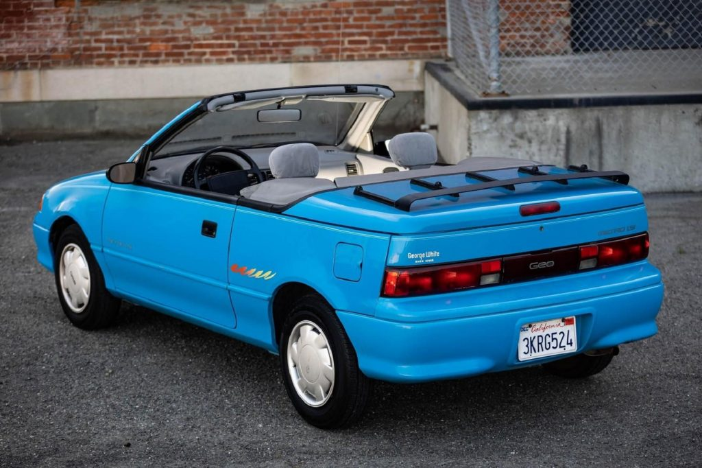 The rear 3/4 view of a blue 1992 Geo Metro LSi Convertible parked by a brick building