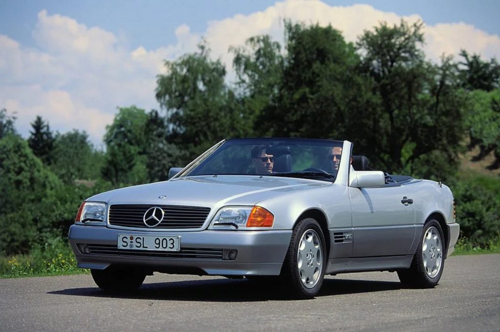 A two-tone silver-and-gray 1992 R129 Mercedes-Benz 600 SL driving down a country road