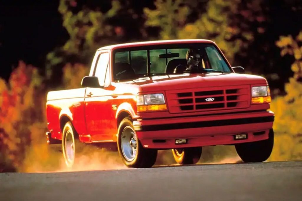 A red 1993 Ford SVT F-150 Lightning kicks up some dust driving down the road