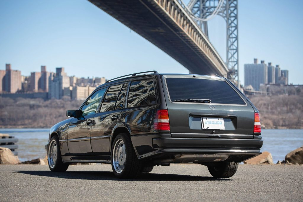 The rear 3/4 view of a black 1993 W124 Mercedes-Benz 320TE Wagon with the AMG kit by a NYC bridge