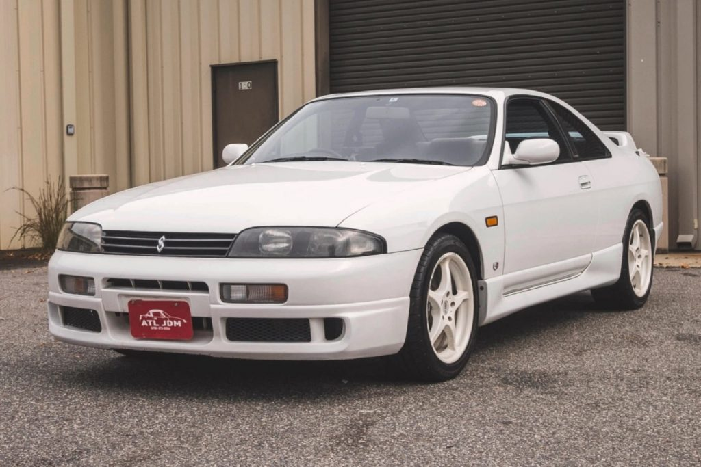 A white 1994 R33 Nissan Skyline GTS-25t parked by a building