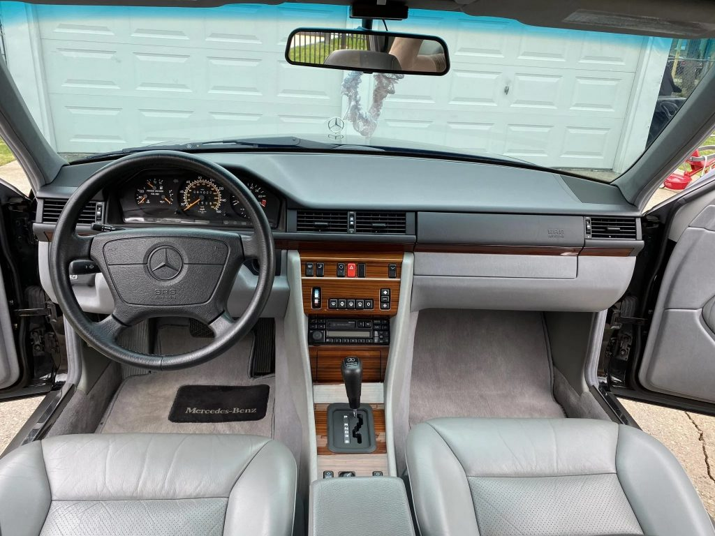 The gray-leather front seats and dashboard of a 1995 W124 Mercedes-Benz E320