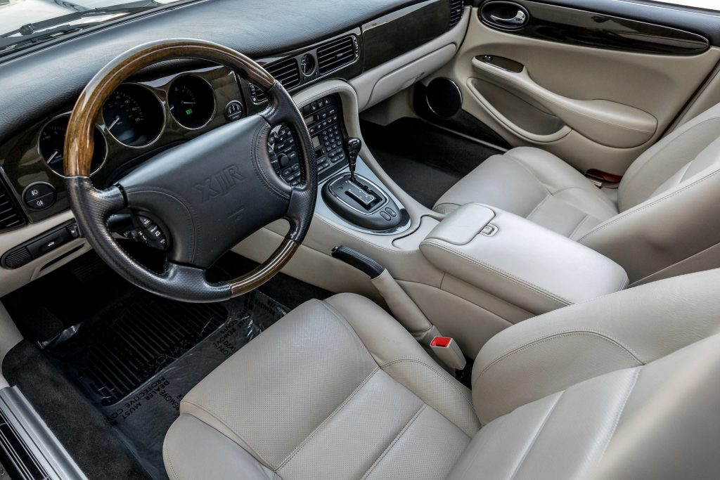 The white-leather front seats and dark-wood-trimmed dashboard of a 1998 Jaguar XJR