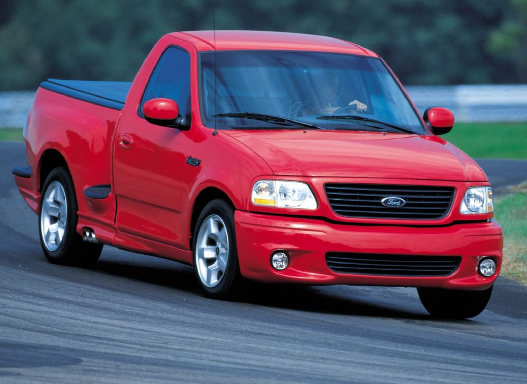 A red 2001 Ford F-150 SVT Lightning drives around a corner of a racetrack