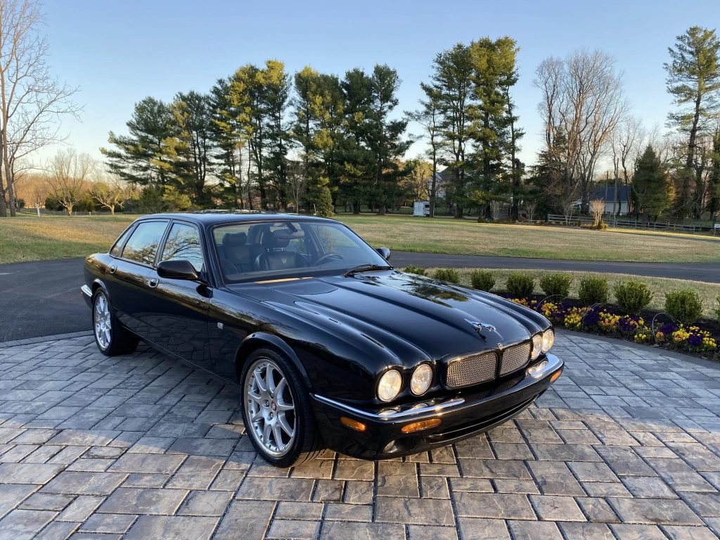 A black 2002 Jaguar XJR 100 on a stone driveway in front of a tree-lined lawn