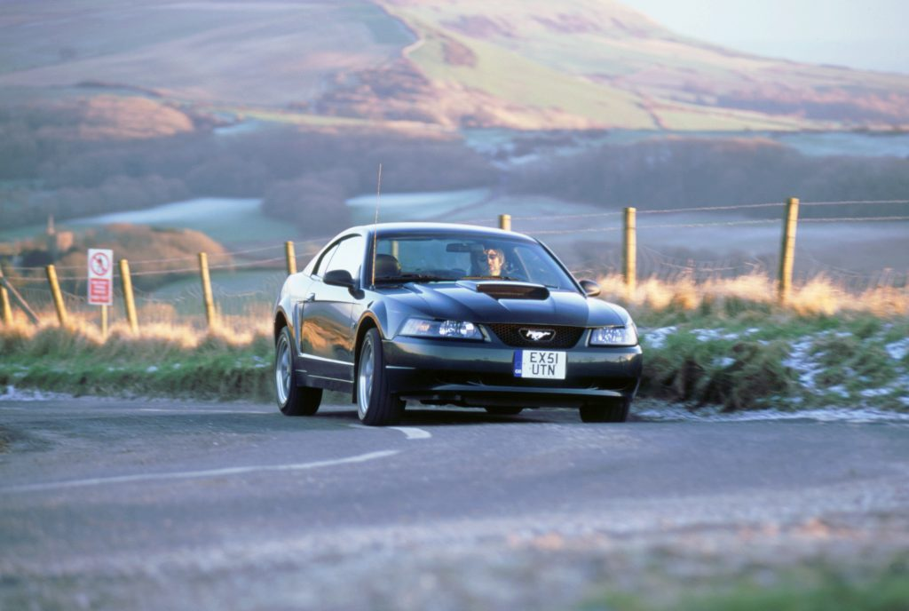 2002 Ford Mustang Bullitt cornering on a country road.
