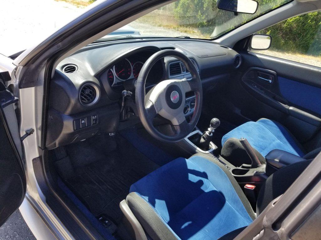 The blue-and-black front sport seats and black dashboard of a 2004 Subaru Impreza WRX STi