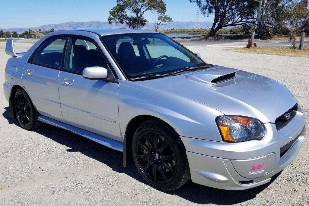 A silver 2004 Subaru Impreza WRX STi in a dirt parking lot