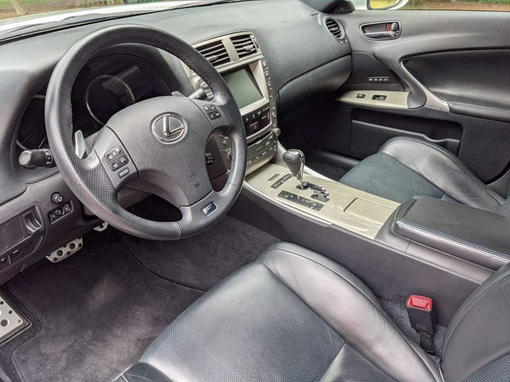 The blue-and-black-leather front seats and gray dashboard of a 2008 Lexus IS F