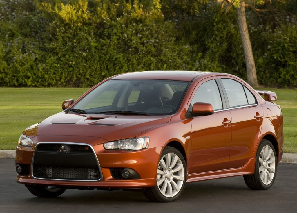An orange 2009 Mitsubishi Lancer Ralliart parked by a hedge-lined lawn