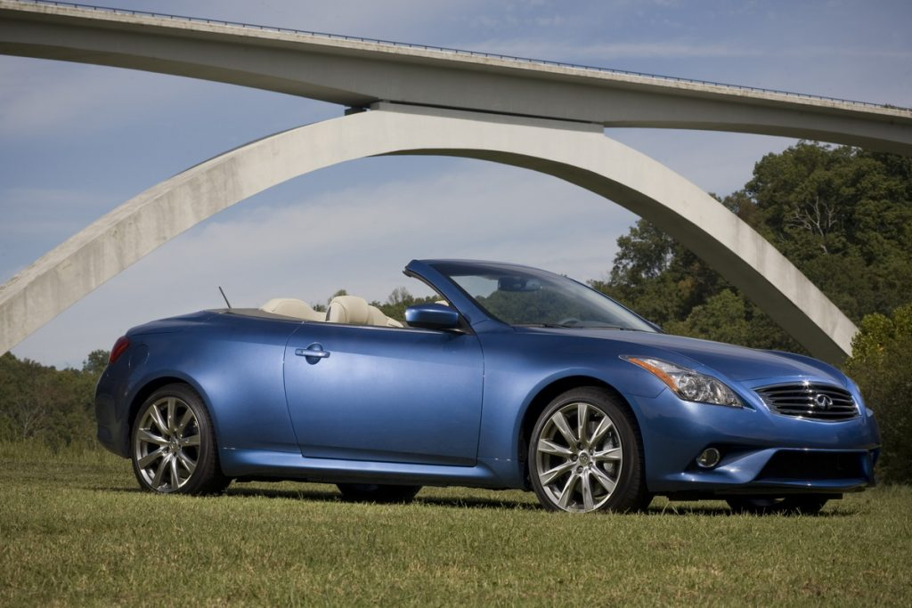 A blue Infiniti G convertible sits on grass photographed from the front 3/4