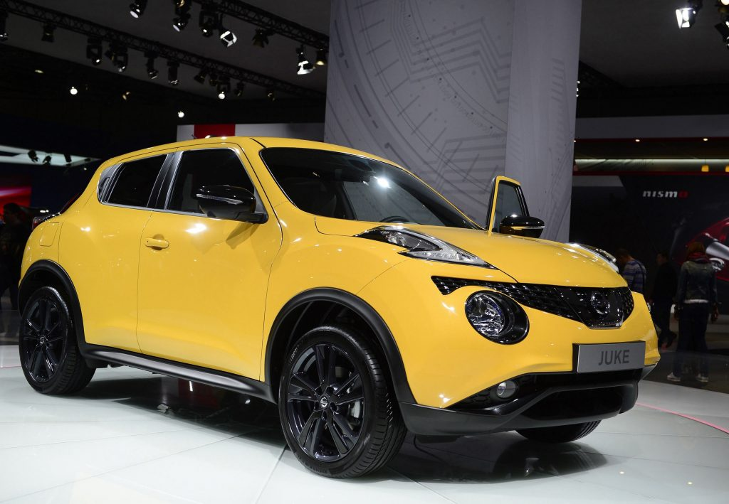 A shiuny yellow Nissan Juke is in the spotlight at the Moscow Automobile Salon.
