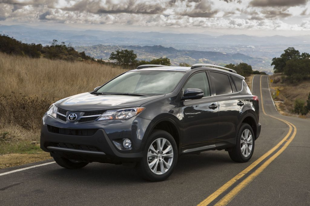 A grey 2015 Toyota RAV4 parked in the street, the RAV4 is among the best affordable used SUVs for teens under $20,000
