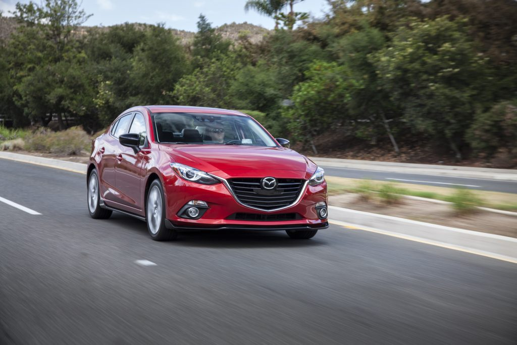 The red 2016 Mazda3 rolls down the road with trees passing in a blur in the background