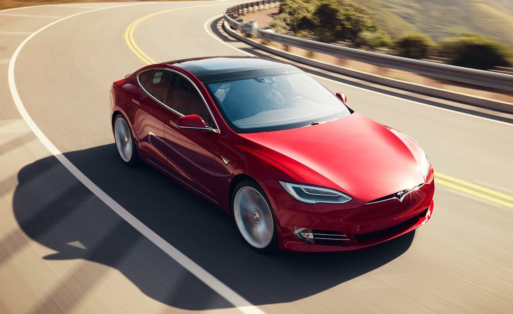 A red Tesla Model S on the open road