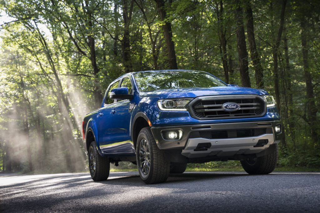 A blue 2020 Ford Ranger parked on a sun-dappled road in a forest