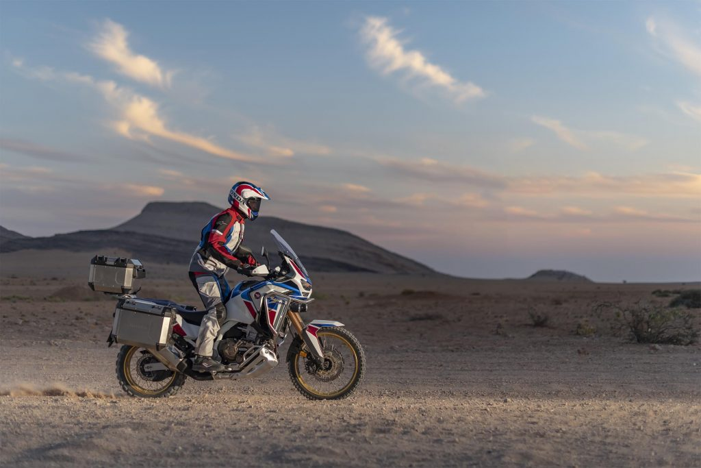The side view of a white-red-and-blue-clad rider taking a white-red-and-blue 2020 Honda Africa Twin Adventure Sports ES DCT through a desert