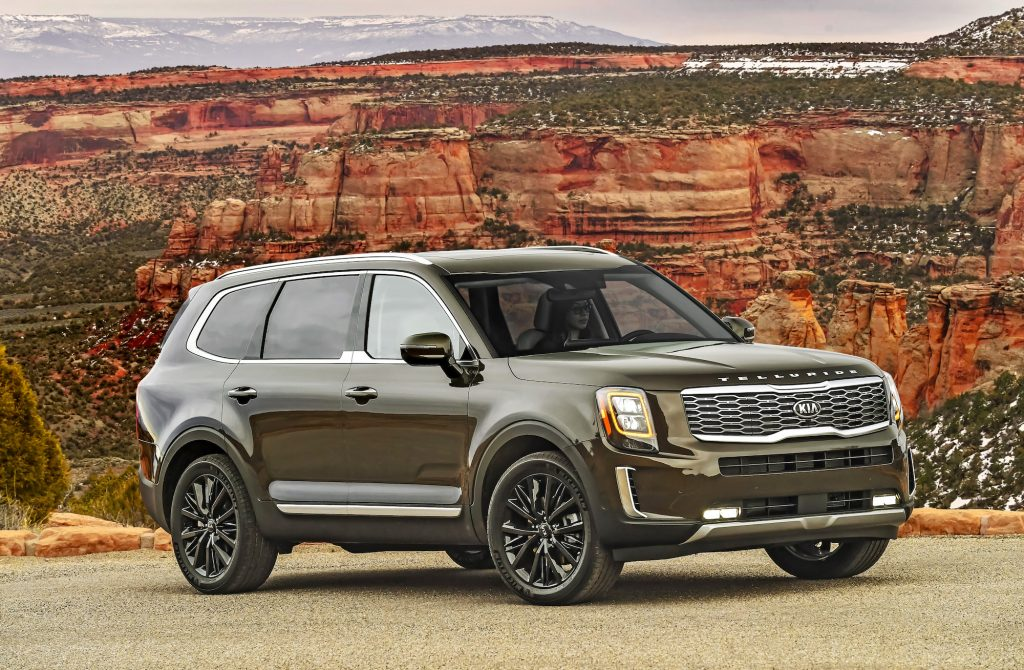 A dark-green 2020 Kia Telluride midsize crossover SUV parked in front of a red butte and mountains