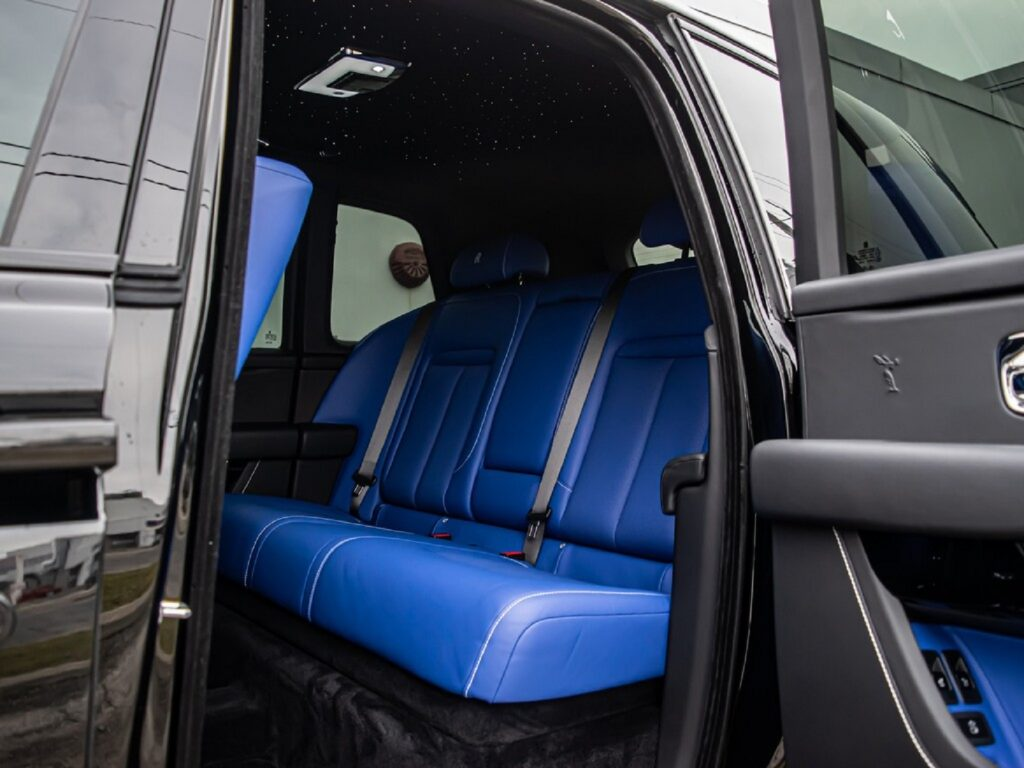 The blue-leather rear seats and Starliner headliner in a black 2020 Rolls-Royce Cullinan Black Badge